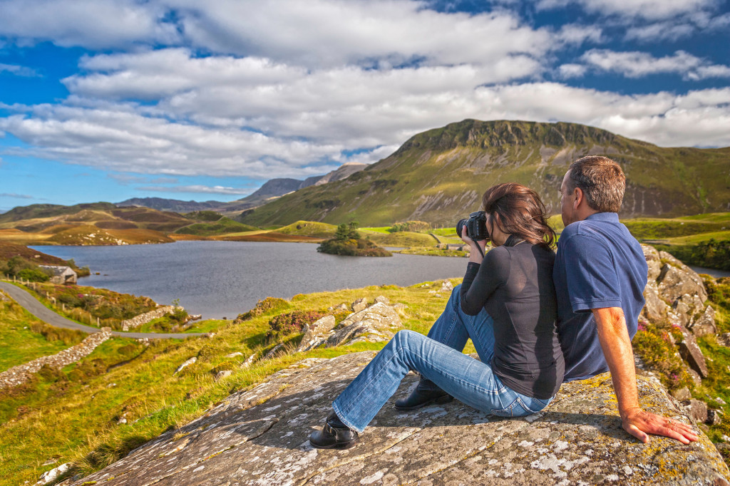 Couple resting with woman taking photograph, with lakes and Cadair Idris in background Llynnau Cregennen Snowdonia Gwynedd Mid Walking Activities and Sports